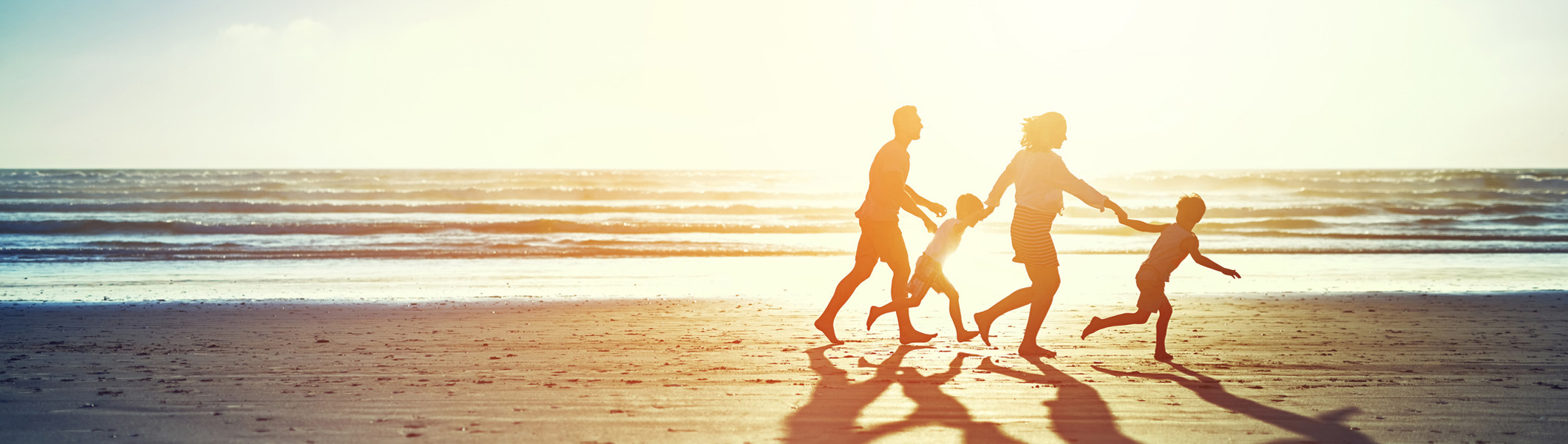 Family walking on beach holding hands, in silhouette from sunset