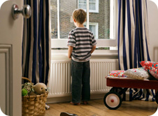 Young boy looking out over windowsill