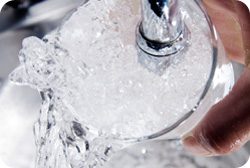 Filling a glass of ice at a faucet
