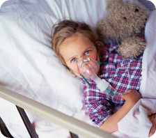 Young girl receiving breathing treatment in hospital bed
