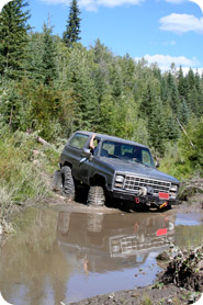 An off-road vehicle bogged down in mud