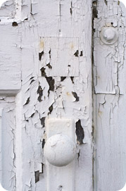 Paint flaking off of an old door with handle