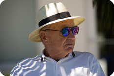 Elderly man in hat and sunglasses in shade