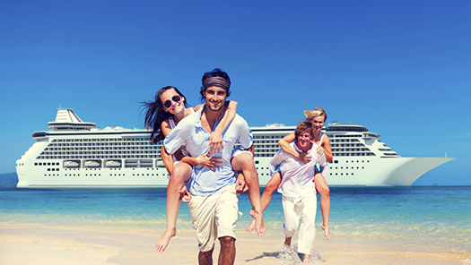 Couples on beach with cruise ship behind them