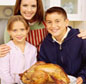 Mother and children holding cooked turkey