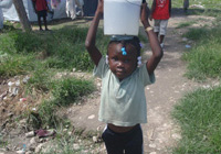 Photo: Haitian girl with water bucket on head