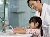Mother teaching daughter to wash hands