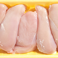 Pieces of raw chicken in a container.