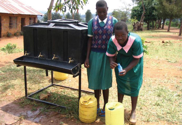 Image of Two members of the safe water club at Sino SDA Primary School in Nyanza Province in rural Kenya treating the school drinking water with Water¬Guard.