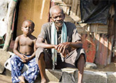 Older African Male with young boy sitting in village