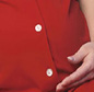 Pregnant lady in red shirt holding stomach