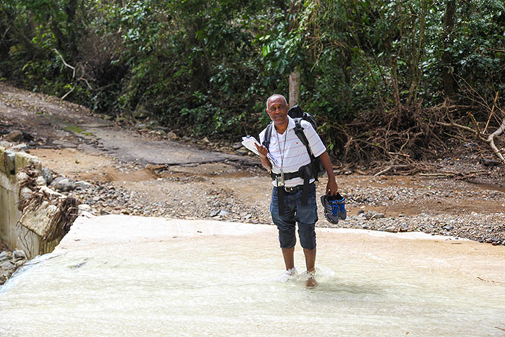 CDC employee Tesfaye Bayleyegn crosses a river to reach houses in the isolated community of Barrio Coamo Arriba in Coamo, Puerto Rico. Photo by Ashley Andujar.