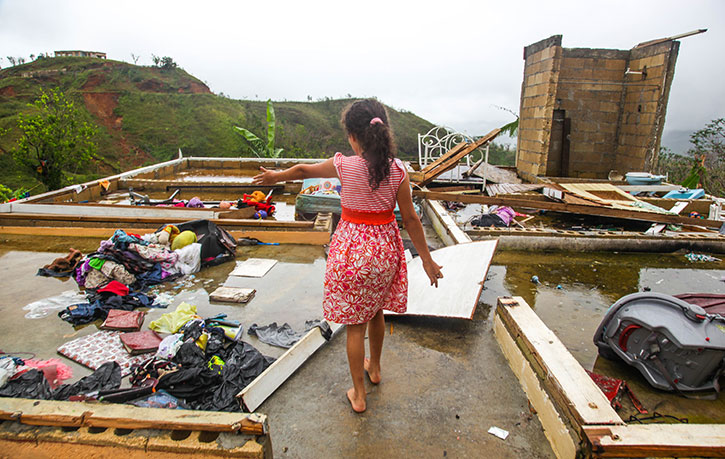 A young girl shows her hurricane-battered home in Jayuya, Puerto Rico.