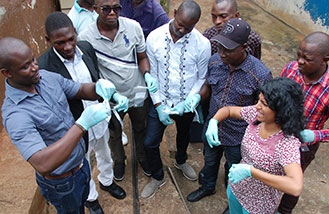 CDC environmental microbiologist Gouthami Rao showing how to collect a water sample