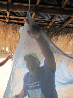 A man inspects a mosquito net. Splenomegaly is often caused by chronic, repeated malaria infections.