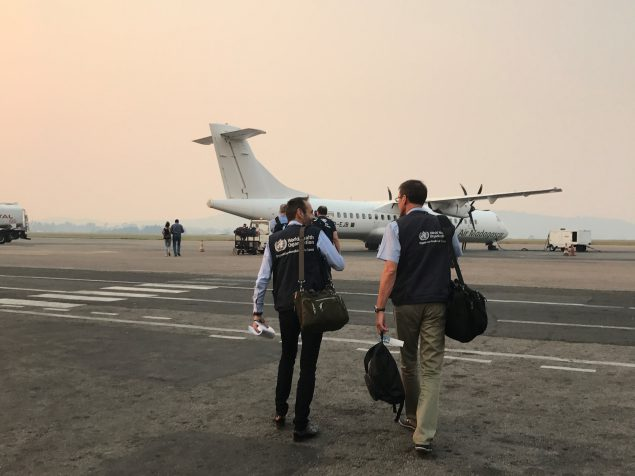 Two men from the back representing the World Health Organization. The two men in the foreground are carrying travel bags, wearing blue WHO vests, and walking across the tarmac towards a prop plane. There are four other people and mountains with a hazy skyline in the distance.