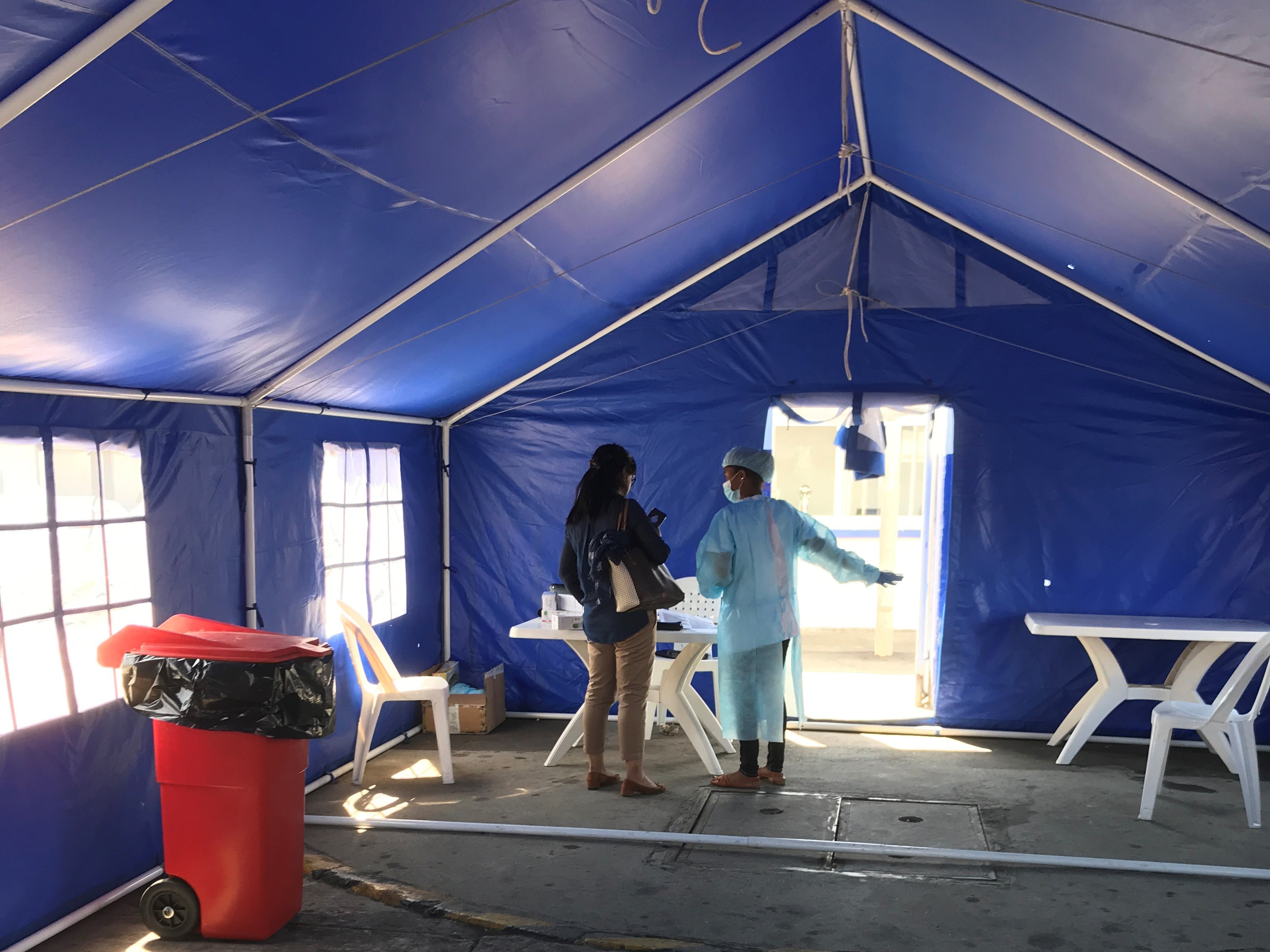 Blue tent with a red biowaste bin and a woman speaking with a person suited up in personal protective equipment.
