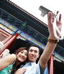 Couple taking a selfie in front of a building in Asia
