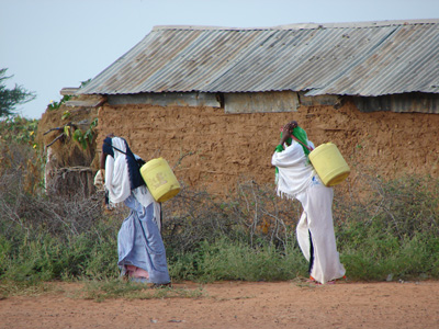 Two women carrying containers of water