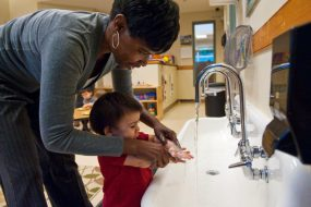 Day care worker helping a toddler wash his hands with soap and warm water