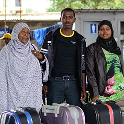 A mother and her two children stand behind their suitcases.
