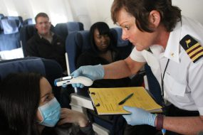 A CDC public health officer checks the temperature of a sick passenger onboard a flight that just landed in Chicago. Photo credit to Erin Rothney.