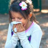 A girl covers her nose and mouth wiht a tissue while sneezing.