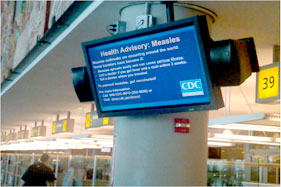 An electronic monitor at O'Hare International Airport displaying measles health advisory.