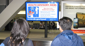 Man and woman at an airport reading a MERS-CoV health advisory on a TravAlert monitor