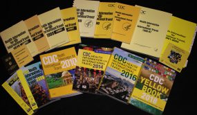 17 different CDC Yellow Book editions fanned out in two different stacks with the older editions in the top stack and the newer editions in the bottom stack.