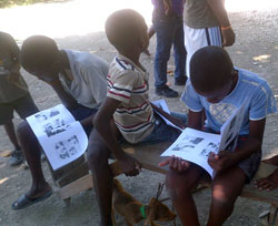 Children read an informational comic book that teaches lessons on rabies.