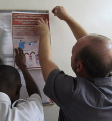 Two men hanging a poster on a wall