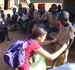 A woman examining a child in Uganda.