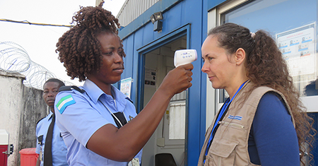 Airport worker using a forehead thermometer to check a passenger's temperature during the 2014 Ebola outbreak in West Africa
