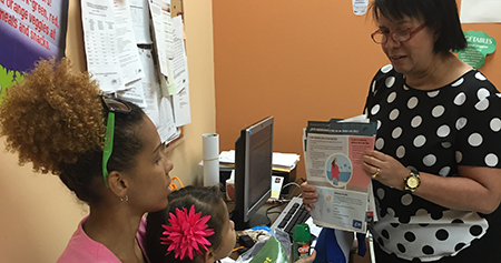 Healthcare worker providing patient education about Zika to a mother and her child.