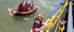 thumbnail image of  a woman from the CDC using a Jacob's ladder to conduct an offshore boarding of a vessel with US Coast Guard and Customs and Border Protection partners. A boat with two more people is seen in the background