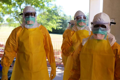 Image of people in yellow protective gear, complete with face masks and head covering.