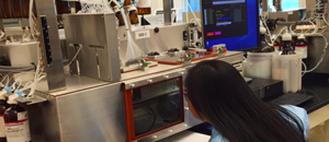 Thumbnail image of a woman leaning in to see a screen as she works in a cdc laboratory.