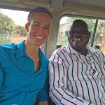 Two smiling epidemiologists sitting on a bus in Uganda