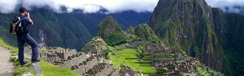Wide landscape image of machu picchu with a hiker at the far left taking a photo of the Inca citadel
