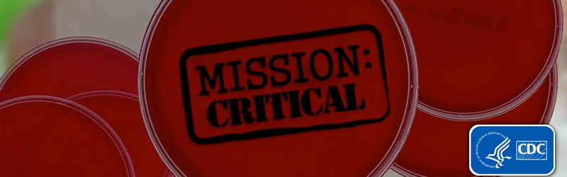 Overlapping petri dishes with red growth medium. The words Mission Critical are stamped on the image.