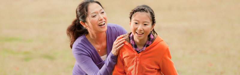 A Japanese mother and daugher smile and play outdoors