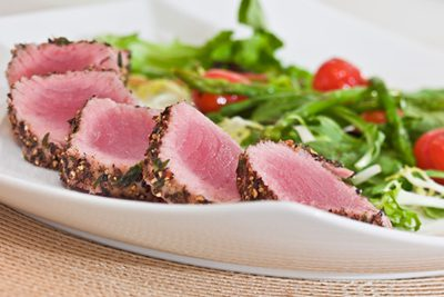 Slices of seared tuna on a plate with vegetables in the background