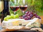Assorted cheeses and grapes on a cutting board with two glasses of red wine in the background.