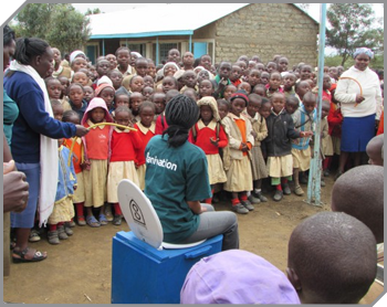 A Sanivation representative named Annette, in a green shirt, demonstrates a Blue Box toilet for a crowd of children and adults in a Kenyan village