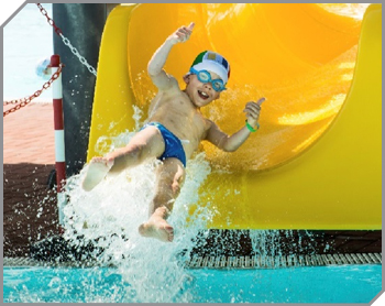 Boy giving two thumbs up as he flies off the end of a yellow waterslide in a big splash of water.