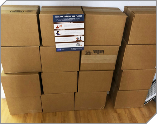Pile of boxes with a handout taped to them - the Healthy Families and Flocks pdf from CDC