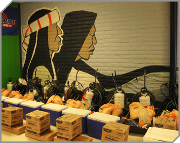 Image of equipment grouped into sets (boxes, orange bags, coolers and a pump spray bottle commonly used for bug treatment) in front of a brick wall painted with a mural  - the profiles of two American Indians