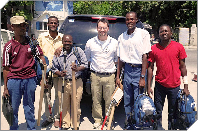 5 men from a rabies team in Haiti and a CDC vet stand with their gear looking at the camera