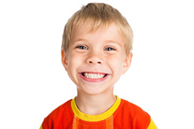 Image of young boy grinning with bright white teeth
